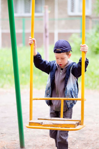 Full length of boy standing on slide in playground