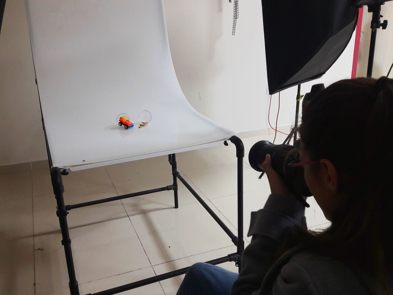 High angle view of young woman photographing toys on chair in studio