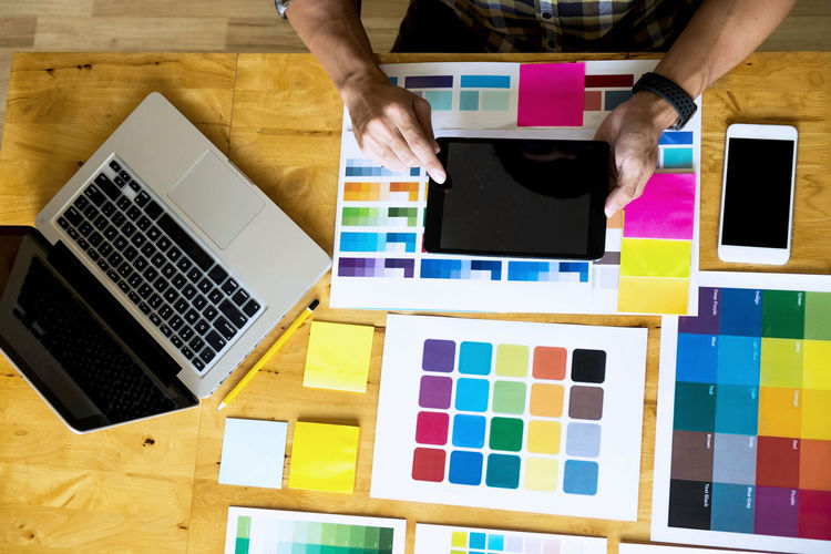 High angle view of businessman using digital tablet over color swatches at desk in office