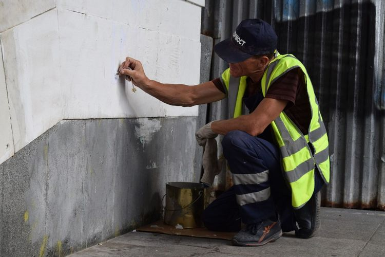 Side view of man working on concrete wall