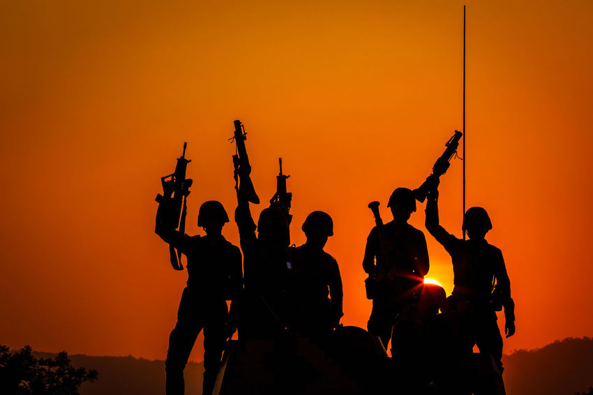 Activity Clear Sky Group Group Of People Gun Holding Land Leisure Activity Lifestyles Medium Group Of People Men Nature Orange Color Outdoors People Real People Silhouette Sky Soldiers Uniform Standing Sunset