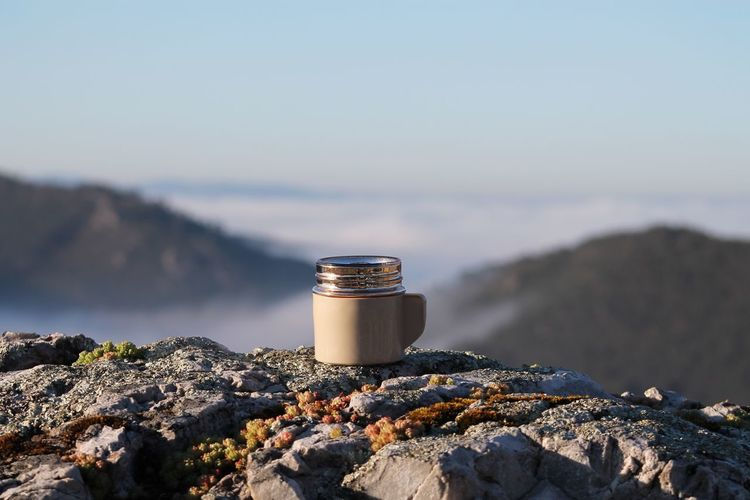 Abandoned lid of insulated drink container on rock against sky