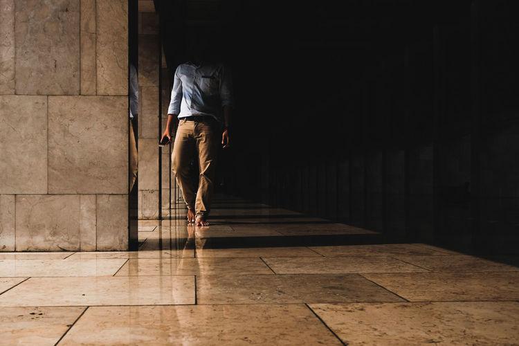 Rear view of man walking on tiled floor
