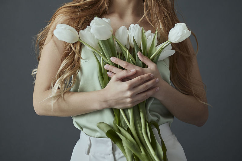 Midsection of woman holding flowers against white background