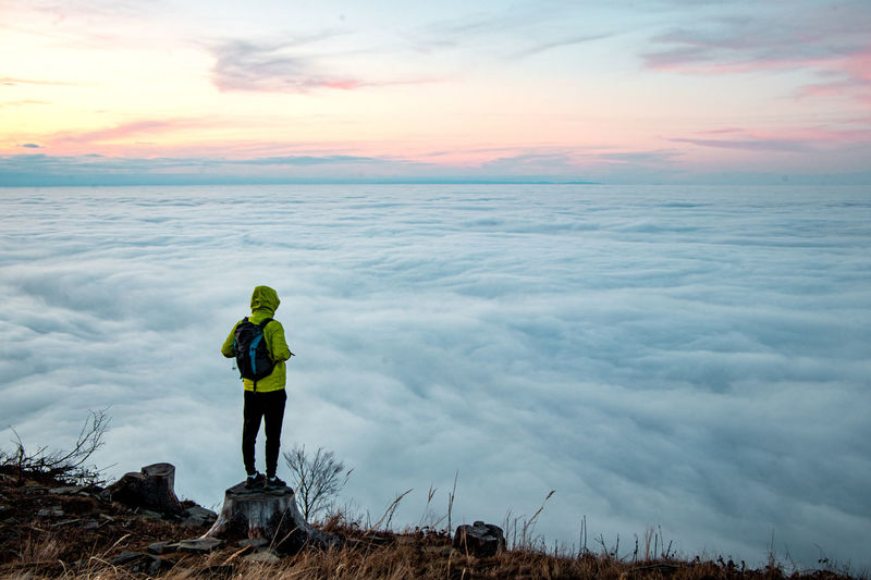 Victory of a young climber after climbing a mountain with a backpack. view of floating clouds