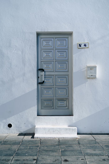 Postcard type photo of metal door number 4 taken in Fuerteventura island. Building Four Home Detail Texture Number 4 Old Design 4 Number Color Architecture Vintage Metal Textured  Abstract Traditional Grunge Close Up Exterior Door Plank Europe Pattern Closed 4 Number Sleek No 4 Entrance Style Wall White Canary Islands Fuerteventura Corralejo Spanish SPAIN Postbox Building Exterior No People House