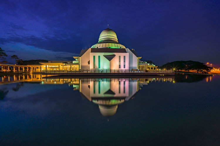 Reflection of illuminated building in lake at night