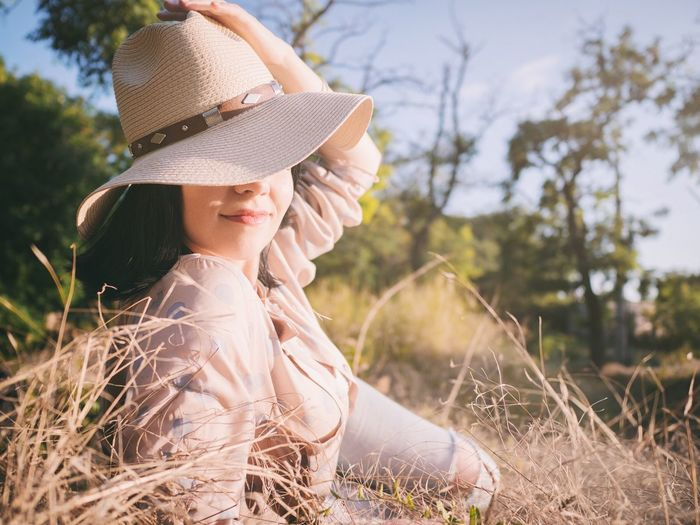 Portrait of young woman in hat against trees