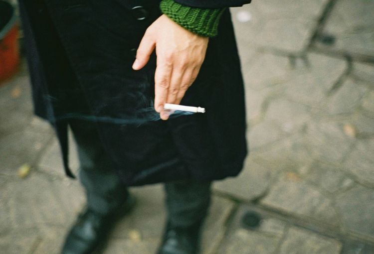 Low section of person holding cigarette on footpath