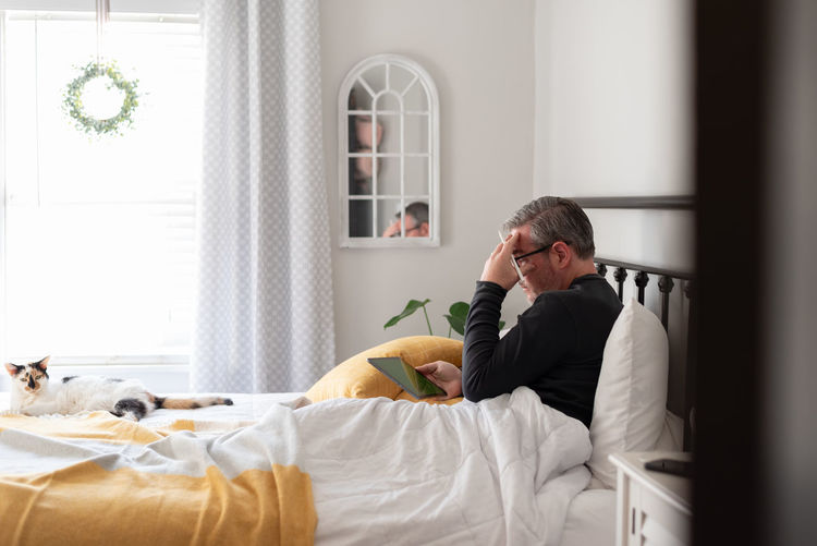 Man sitting on bed at home