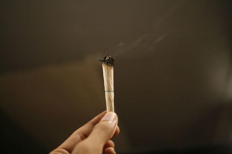 Close-up of hand holding marijuana joint