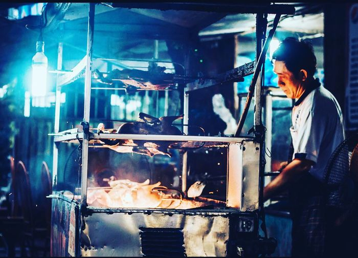 Side View Of Chef Grilling Meat At Food Stall