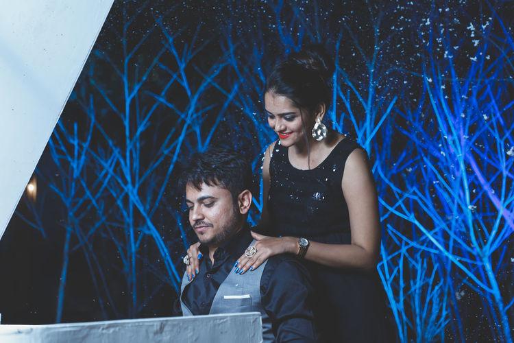 Young couple looking at camera at night
