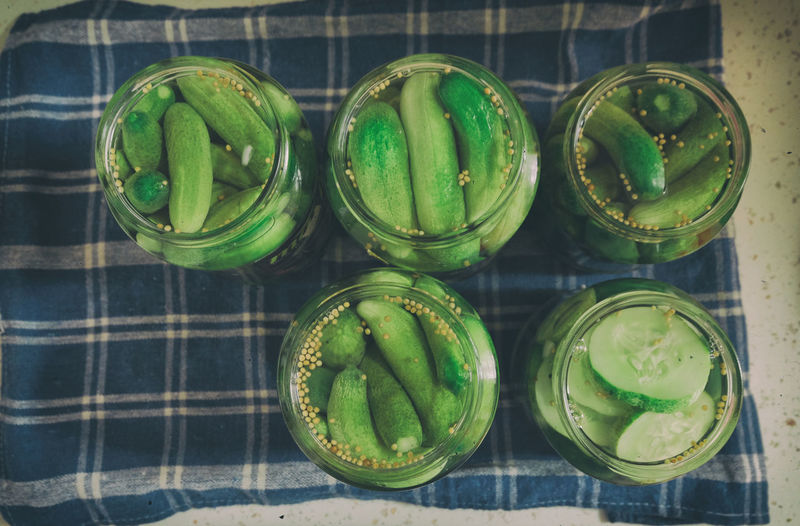 Directly above shot of pickled cucumber in jars on napkin