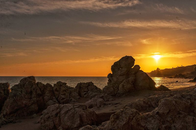 Rock formations on beach against sky during sunset