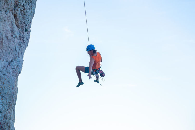 Low angle view of man swinging from rope against clear sky