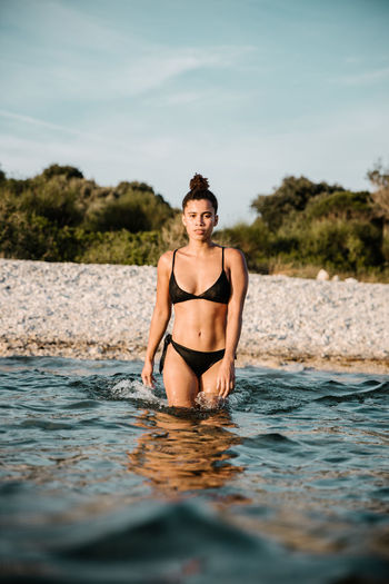 Water One Person Young Adult Lifestyles Real People Front View Portrait Leisure Activity Looking At Camera Clothing Nature Day Sky Swimwear Young Women Bikini Three Quarter Length Outdoors Beautiful Woman