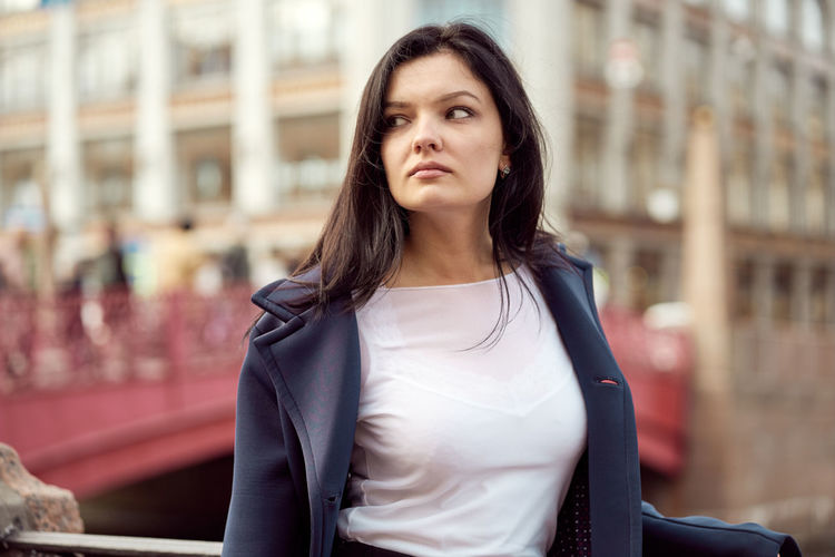 Beautiful young woman standing in city