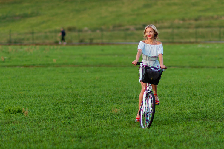 Soft focus photo. A young, beautiful blond woman with a white bike in a green meadow. One Person Day Blonde Young Adult Woman Women Girl Female Beauty Fashion Green Background Eyes Portrait Summer Face People Nature Model Hair Spring Cute Skin Smilling Field Outdoors person Caucasian White Attractive Pretty Smile Season  Elégance Luxury Glamour Outside Gorgeous Hairstyle Shoulders Design Copy Space Copyspace Modern Bike Bicycle Cicling Basket Biking Grass Green Color Land Transportation Lifestyles Leisure Activity Real People Full Length Casual Clothing Sport Plant Mode Of Transportation Front View Land Vehicle Riding