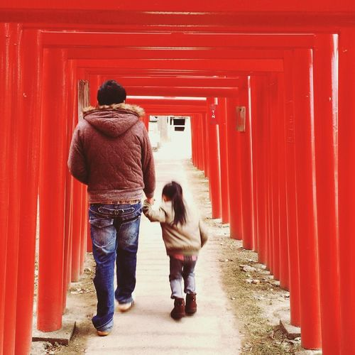 Rear view of couple walking on red road