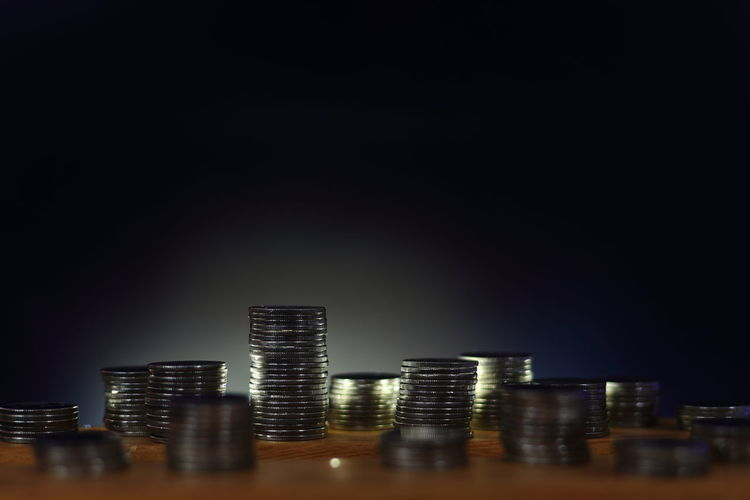 Scattered coins piles on wood plank with back light outlined the tower. saving money and economic
