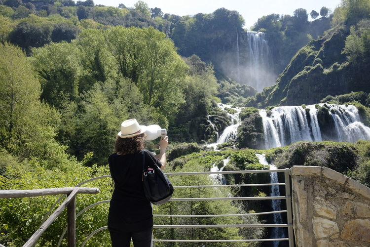 One Person Tree Scenics - Nature Waterfall Beauty In Nature Water Nature Real People Plant Railing Leisure Activity Motion Flowing Water Lifestyles Long Exposure Day Mountain Non-urban Scene Outdoors Looking At View Flowing Power In Nature Binoculars Hat From Behind Woman Tourist