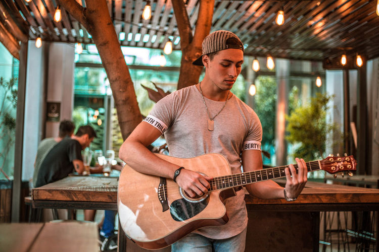 Young man playing guitar in cafe
