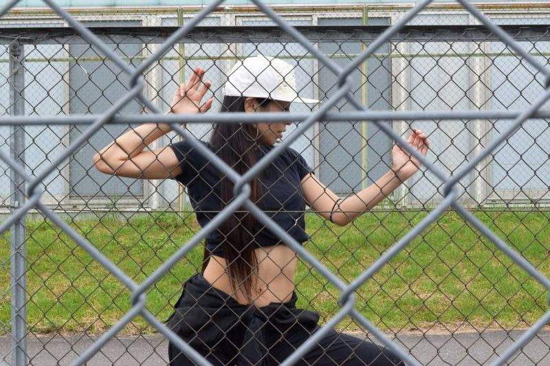 Woman seen through chainlink fence