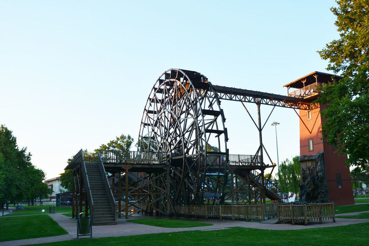 Wheel Amusement Park Amusement Park Ride Architecture Arts Culture And Entertainment Building Exterior Built Structure Clear Sky Copy Space Day Grass Leisure Activity Metal Mill Nature No People Outdoor Play Equipment Outdoors Plant Playground Sky Sport Tree