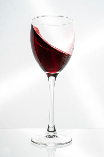 Red wine in glass against white background
