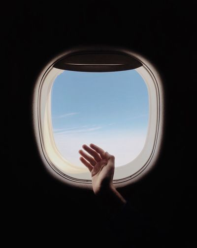 Cropped hand gesturing against airplane window