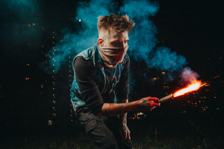 Young man wearing mask holding blow torch at night