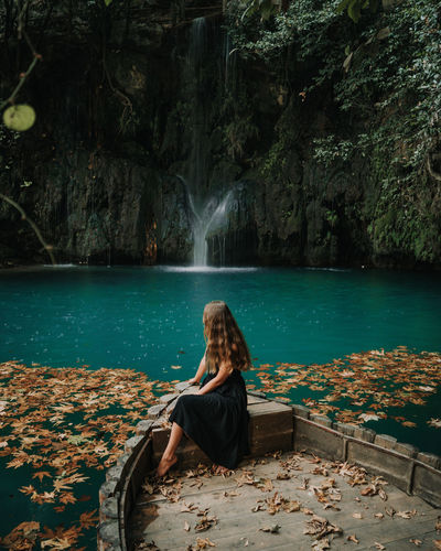 Woman sitting on boat by waterfall