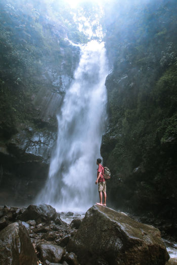 Side view of young man with backpack looking at waterfall while standing on rock