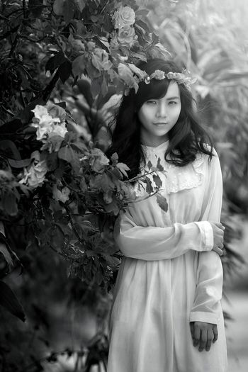 Portrait of woman wearing tiara while standing by plants