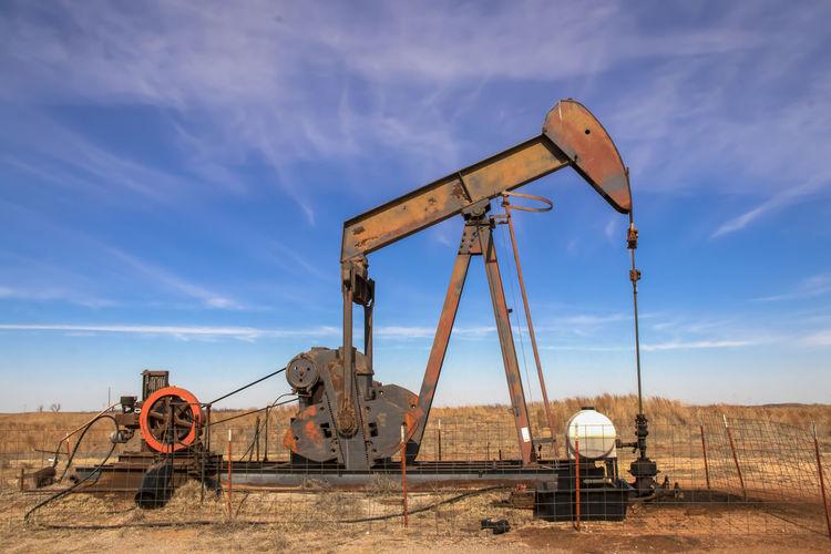 Oil well against sky