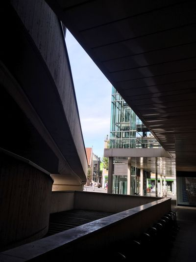 Low angle view of bridge amidst buildings against sky