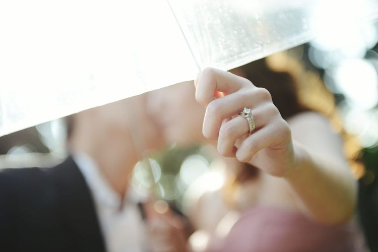 Close-up of couple kissing under umbrella