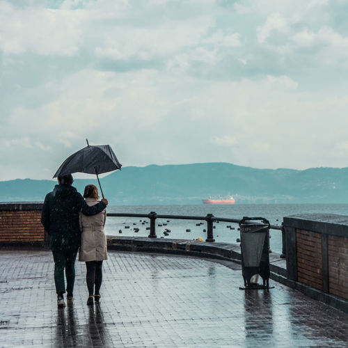 Couple Relationship Lovers Rain Rainy Days Umbrella Mediterranean Sea Seaside_collection Cloudy Day Clouds Nautical Vessel Boat Water Men Adult Protection Two People Full Length Real People Women People Togetherness Couple - Relationship Outdoors Sky Cloud - Sky Wet Nature Rear View Sea Rainy Season The Art Of Street Photography
