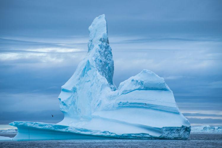 View of ice berg in sea against sky
