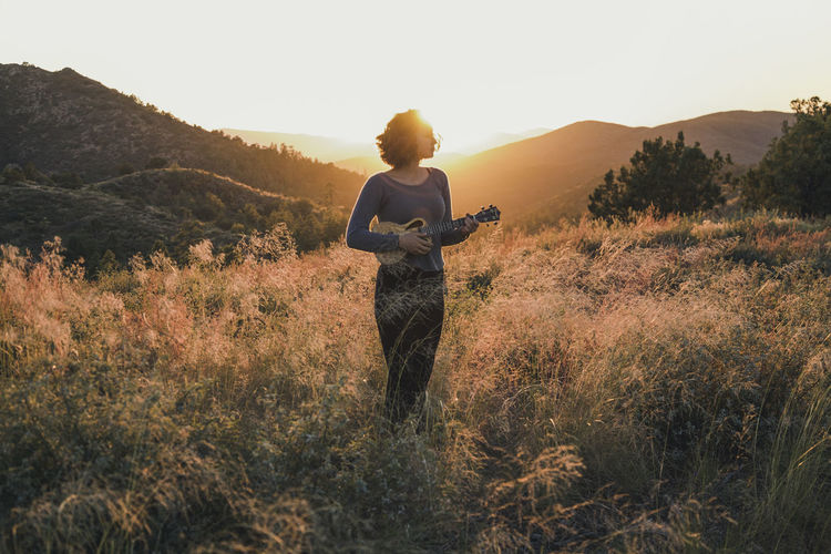 A woman stands in the mountains in the setting sun with her ukulele Orange Profile Adventure Backlit Beautiful Woman Beauty In Nature Clear Sky Evening Sky Grass Hiking Lifestyles Mountain Mountains Musical Instrument Musician Nature One Person Outdoors Silouette Sky Sunset Tree Ukulele Young Adult Young Women
