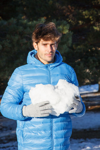 Portrait of young man holding snow standing outdoors