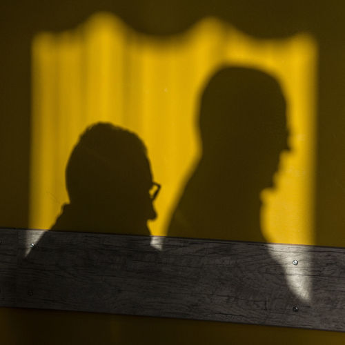 Shadow Of Men On Yellow Wall