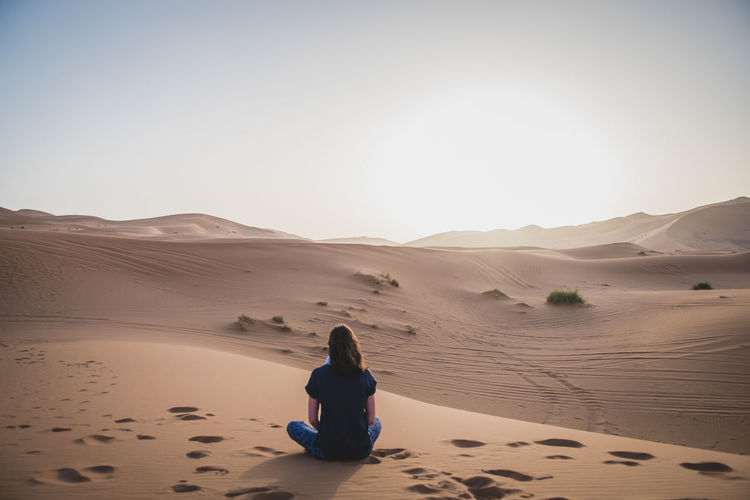 Rear view of woman sitting on desert against sky