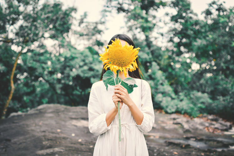 Woman holding yellow flower