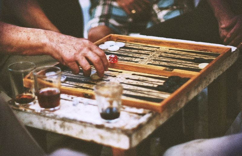 Midsection view of men playing backgammon