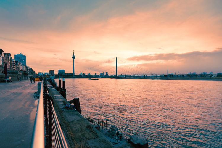 Duesseldorf, GERMANY - February 09, 2019: Vivid sunlight breaks through grey winter sky and iluminates the Rhine promenade Sky Architecture Built Structure Sunset Cloud - Sky Water Transportation Bridge Bridge - Man Made Structure Building Exterior Connection Travel Destinations Nature City Travel River Suspension Bridge Tourism No People Outdoors Bay