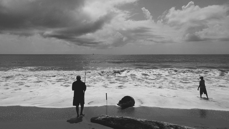 Rear view of men fishing at beach against cloudy sky