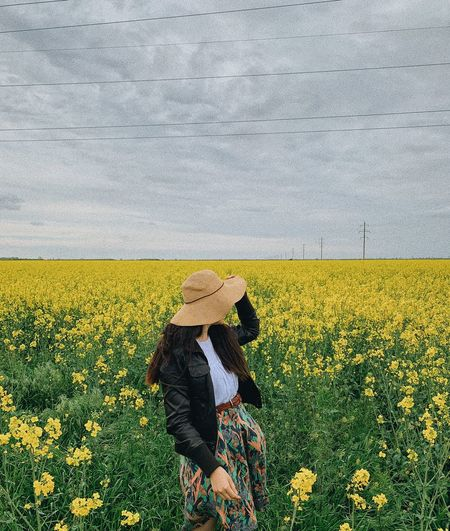 Person standing on yellow flower field