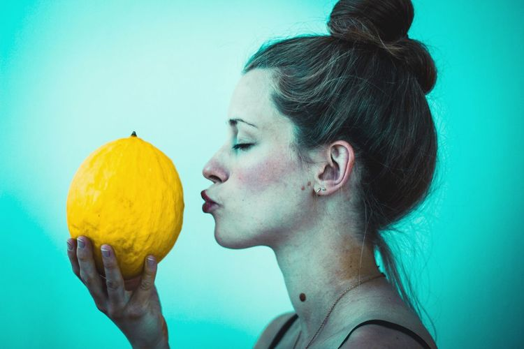 Profile view of woman kissing cantaloupe against turquoise background
